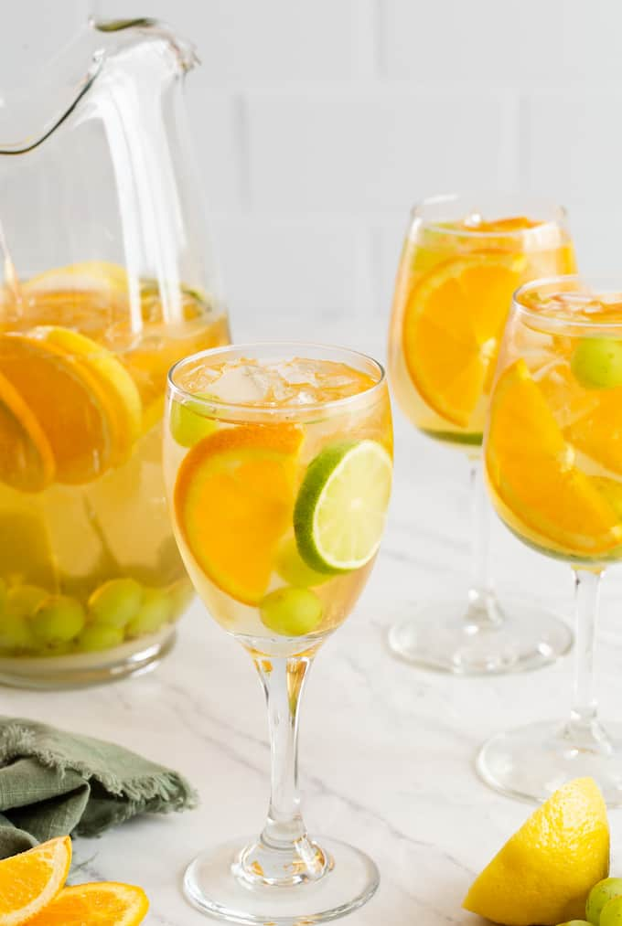 Three wine glasses filled with a fruity white sangria with orange and lime slices and grapes mixed in and a pitcher to the side
