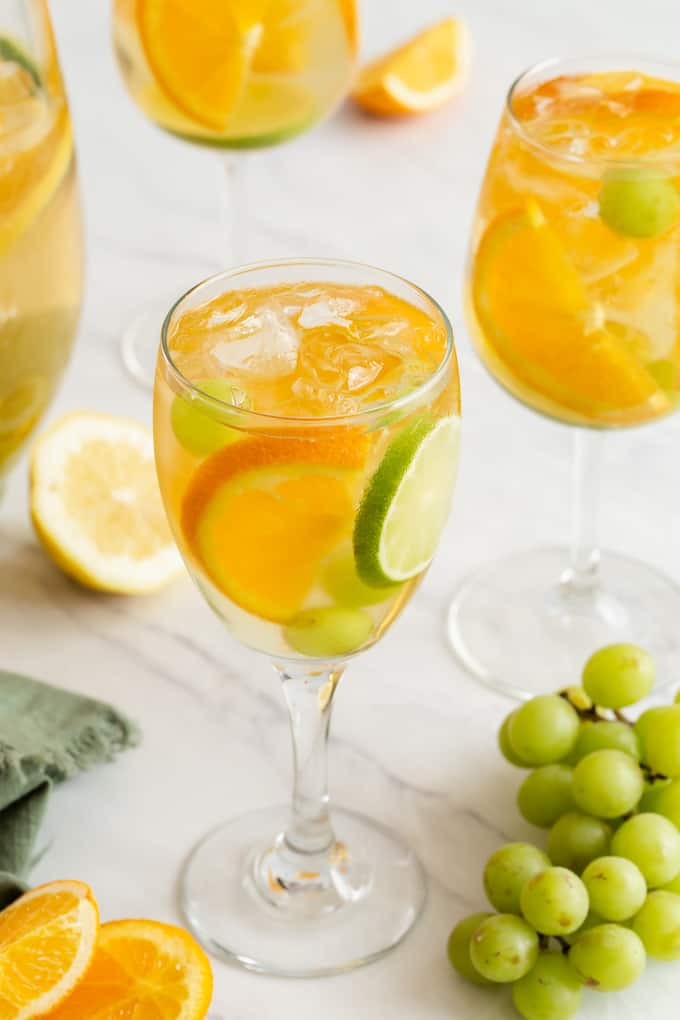 Two wine glasses filled with a sparkling white sangria, grapes, orange and lime slices