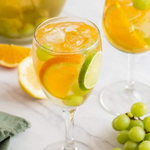 Two wine glasses filled with a white sparkling sangria, grapes, orange and lime slices and a pitcher in the background