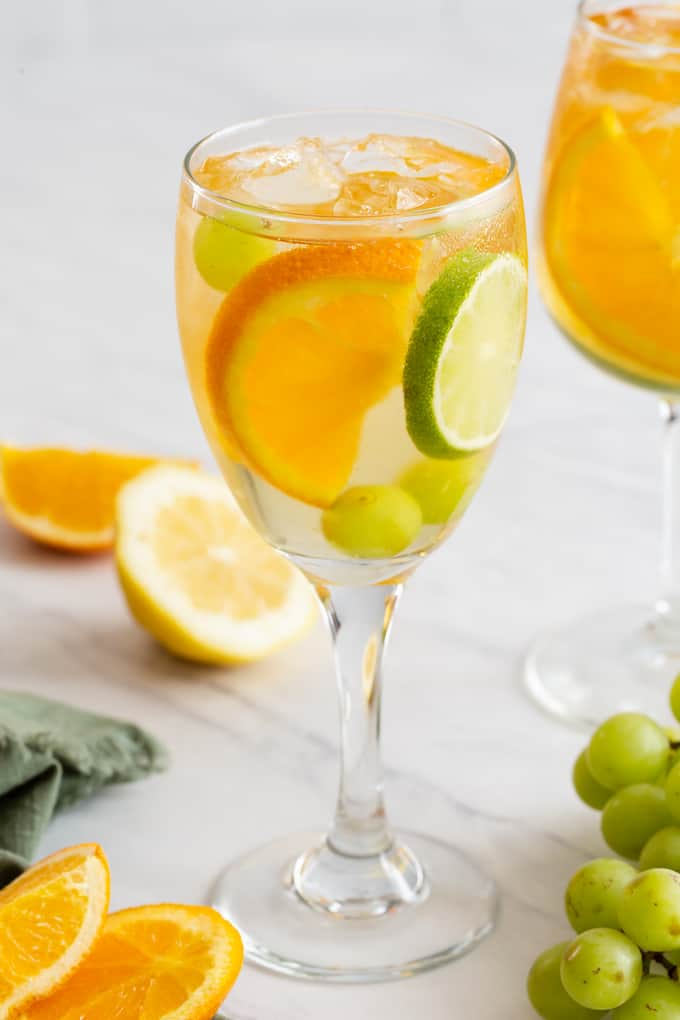 A wine glass filled with a white sangria, grapes, orange and lime slices and extra fruit lying nearby