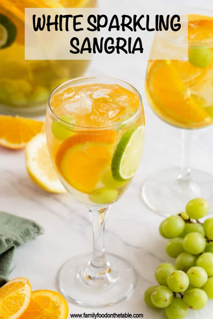 A wine glass filled with a white sangria, grapes, orange and lime slices with a text overlay on the photo