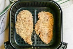 Two breaded chicken cutlets in an Air Fryer insert before being cooked