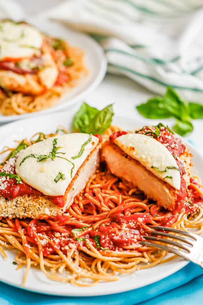 A breaded chicken cutlet with marinara and mozzarella sliced in half on a plate with spaghetti noodles