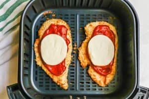 An Air Fryer with two chicken Parmesan cutlets with marinara and mozzarella before being cooked