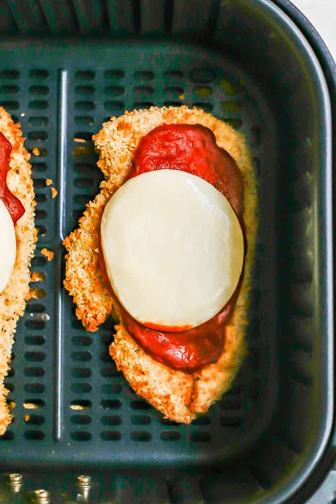 A crispy chicken cutlet with marinara and mozzarella in an Air Fryer tray
