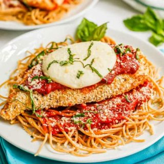 A chicken Parmesan cutlet with marinara, mozzarella and basil served over spaghetti on a white plate
