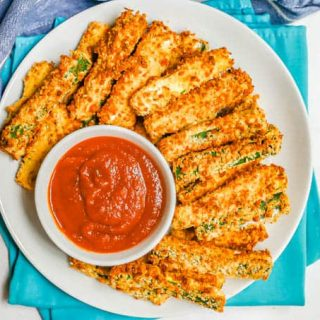 Overhead shot of crispy zucchini fries on a white plate with a small white bowl of marinara sauce