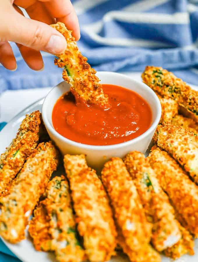 A hand dipping a crispy Air Fryer zucchini stick into a small bowl of marinara