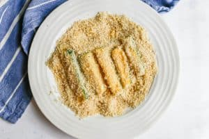 Zucchini sticks being breaded with Panko breadcrumbs in a shallow white bowl