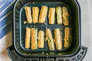 Breaded zucchini sticks in an Air Fryer tray before being cooked