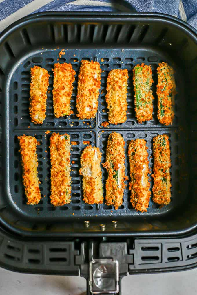 Crispy zucchini fries spaced out and in rows in an Air Fryer tray after being cooked