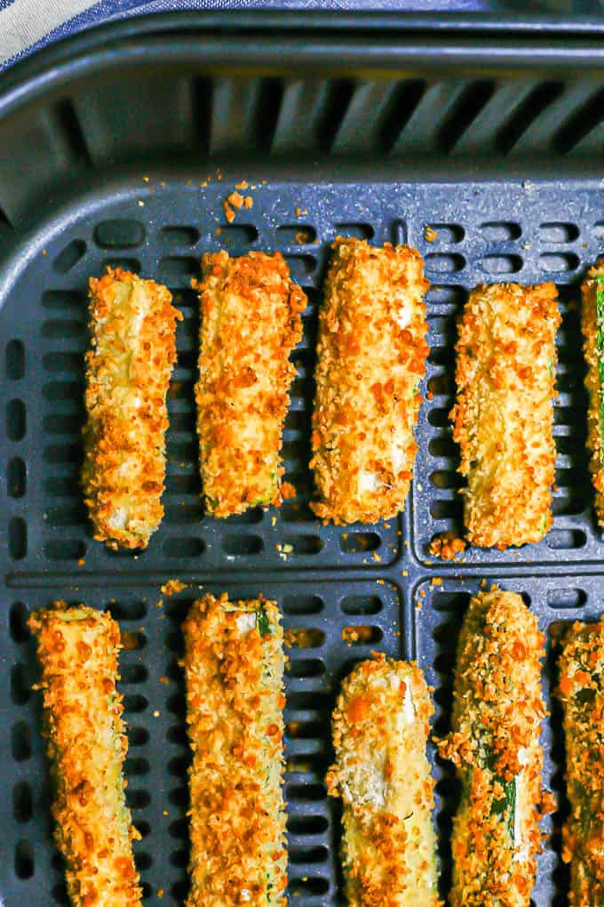 Zucchini sticks spaced out and in rows in an Air Fryer tray after being cooked