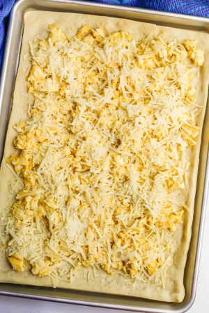 A sheet pan with a pizza dough spread out and topped with scrambled eggs and shredded cheese, before being baked