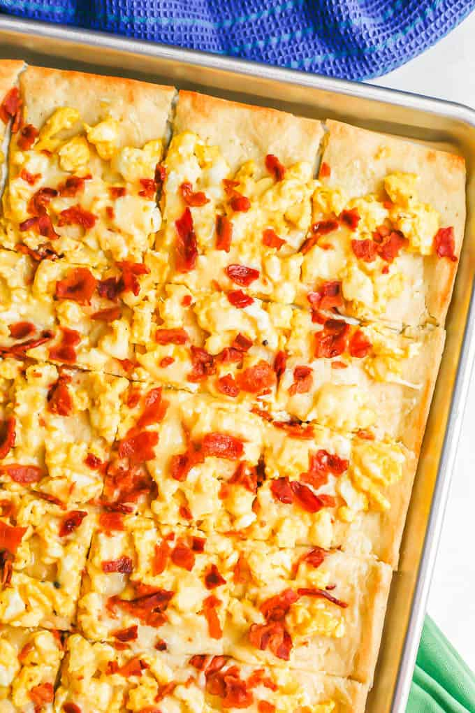 Overhead close up shot of a sheet pan with a cooked pizza with scrambled eggs, bacon and cheese, cut into slices