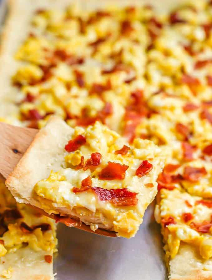 A wooden spatula lifting a slice of egg and bacon breakfast pizza from a sheet pan