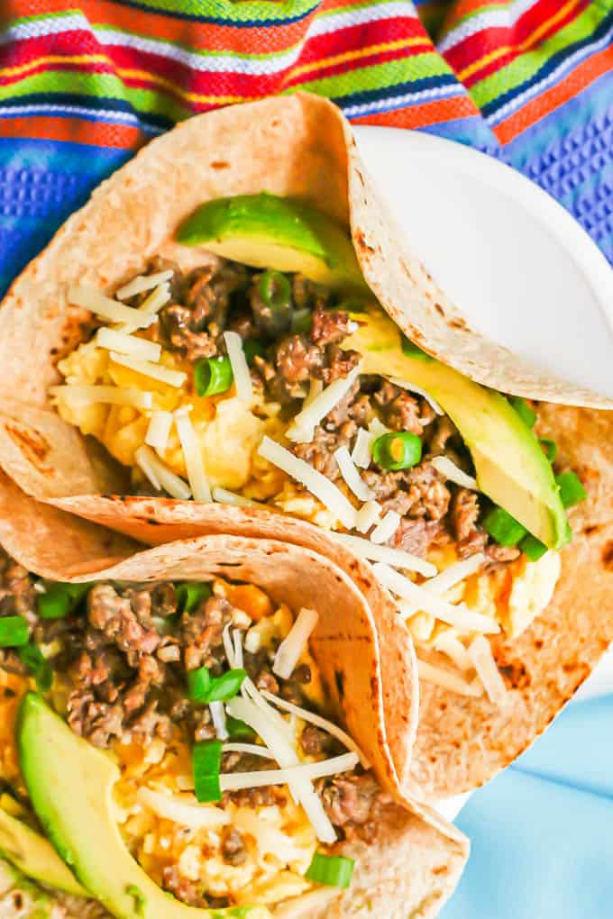 Egg and sausage breakfast tacos in a soft tortilla shell with cheese, avocado and green onion on top