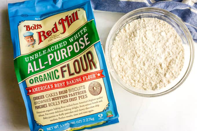 A bag of Bob's Red Mill unbleached white all-purpose flour beside a clear glass bowl of flour