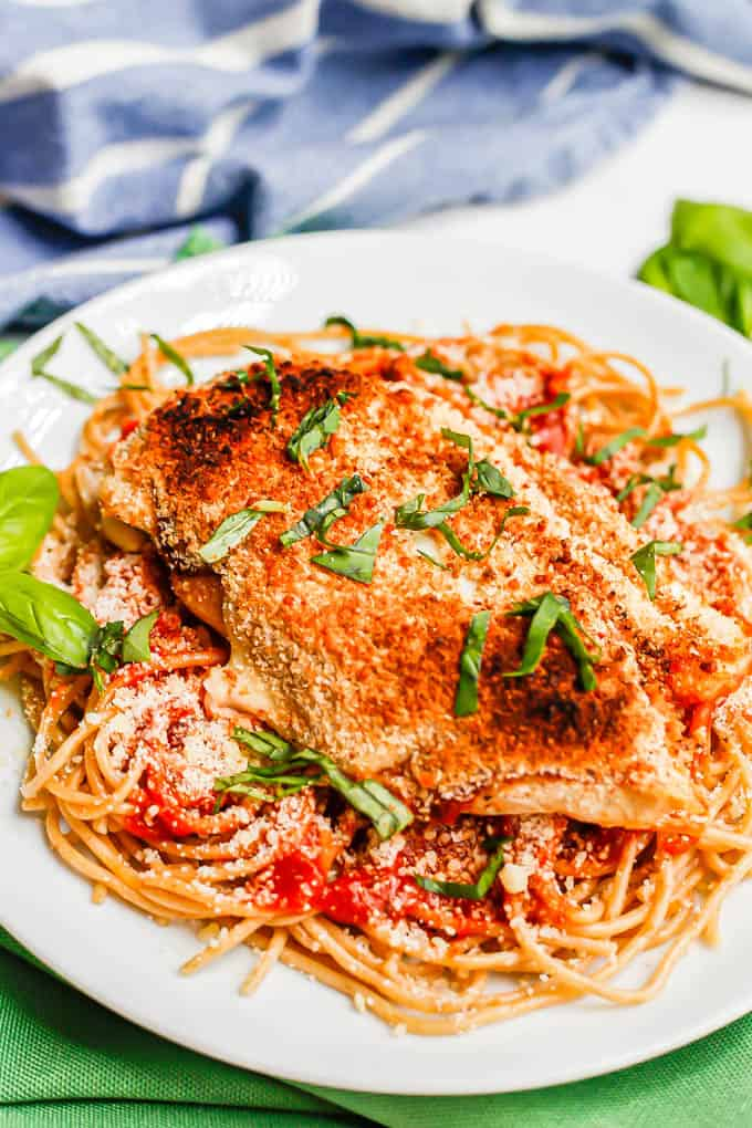 A broiled and browned chicken Parm cutlet served over spaghetti with basil sprinkled on top