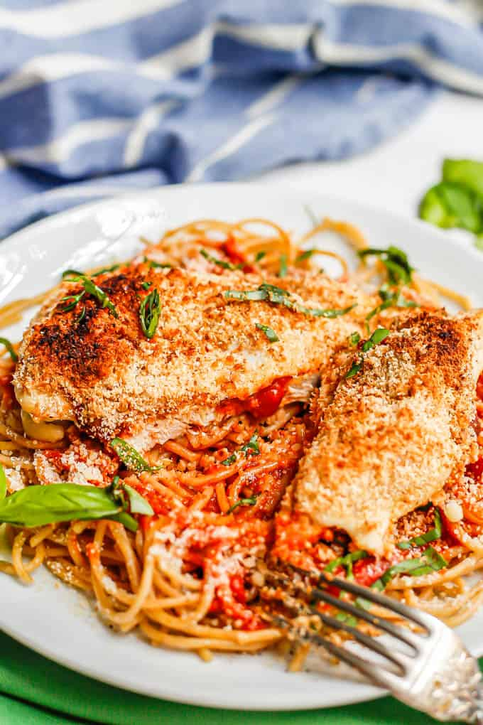 A sliced chicken Parmesan cutlet served over spaghetti noodles with basil sprinkled on top and a fork resting to the side of the plate