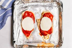 Two halved chicken breasts with marinara and sliced fresh mozzarella on top on a baking sheet