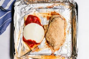 Two chicken breast cutlets with marinara, mozzarella and breadcrumbs on top while in process of being cooked