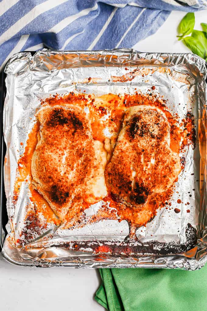 Two browned, broiled chicken Parm pieces on a foil lined baking sheet after being cooked
