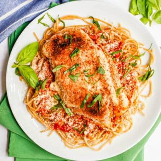 Overhead shot of a plated chicken Parm and spaghetti on a white plate with basil on top