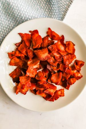 Cooked chunks of crispy bacon on a white plate