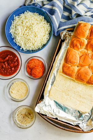 Ingredients to make pepperoni pizza sliders laid out on a counter