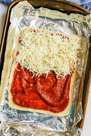 The bottom half of a package of slider rolls topped with marinara sauce and sprinkled halfway with shredded mozzarella cheese