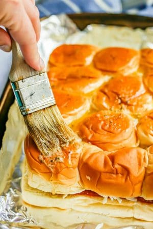 Pizza sliders being brushed with a butter and herb mixture before being baked