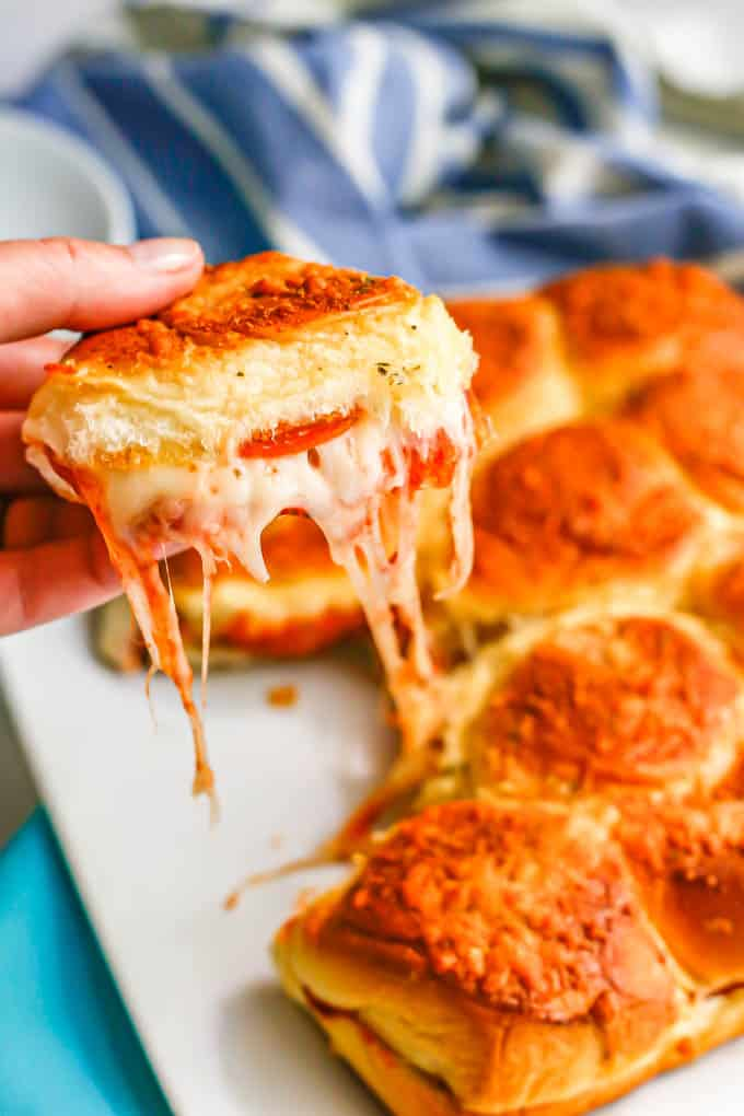 A hand holding up a cheesy pepperoni pizza slider from a plate of sliders