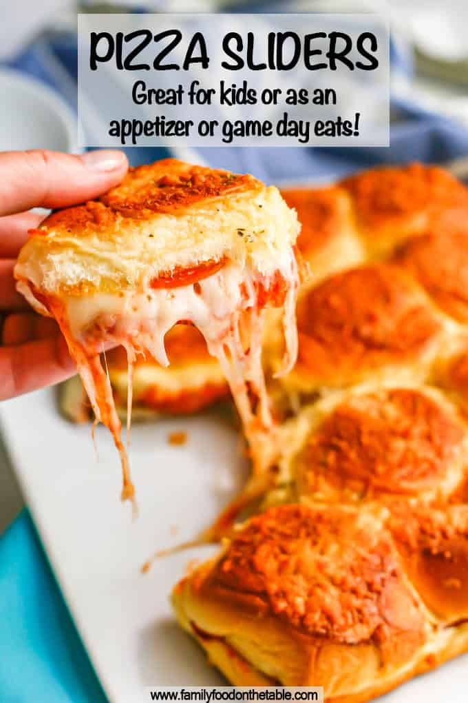 A hand holding up a cheesy pepperoni pizza slider from a plate of sliders with a text overlay on the photo