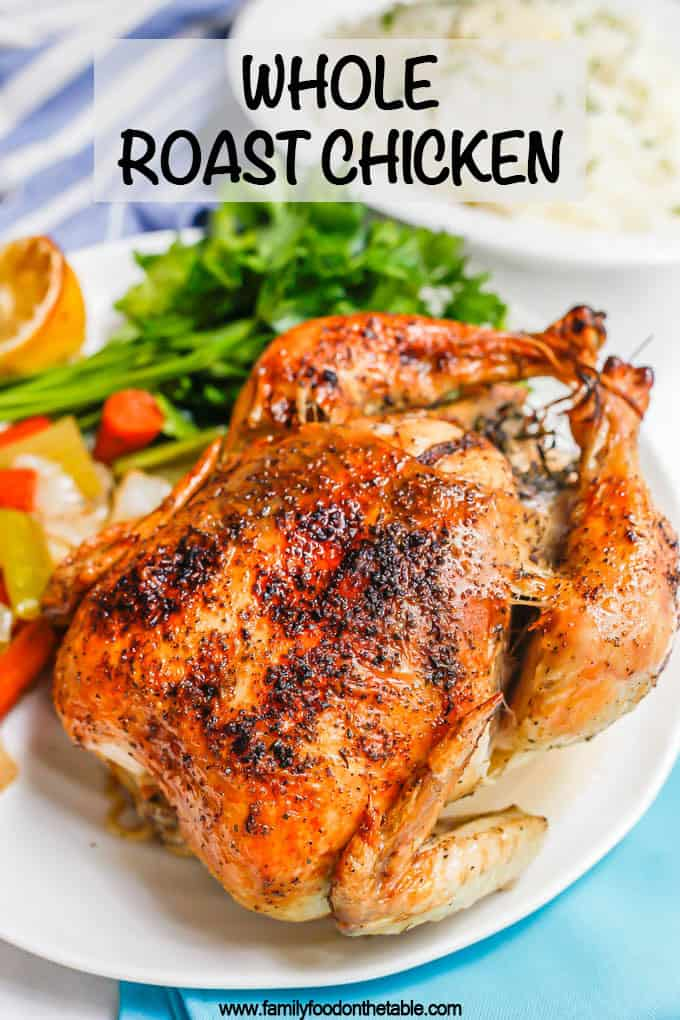 A browned and crispy whole roasted chicken on a platter with roasted veggies and fresh parsley with a text overlay on the photo
