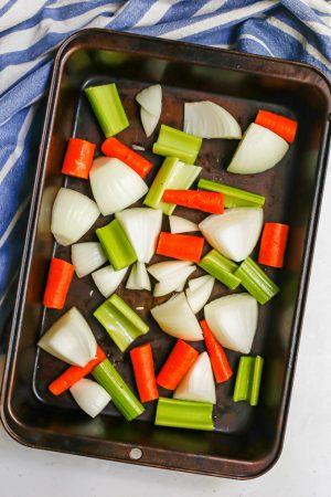 A mix of raw carrots, celery and onion in a roasting pan before being cooked