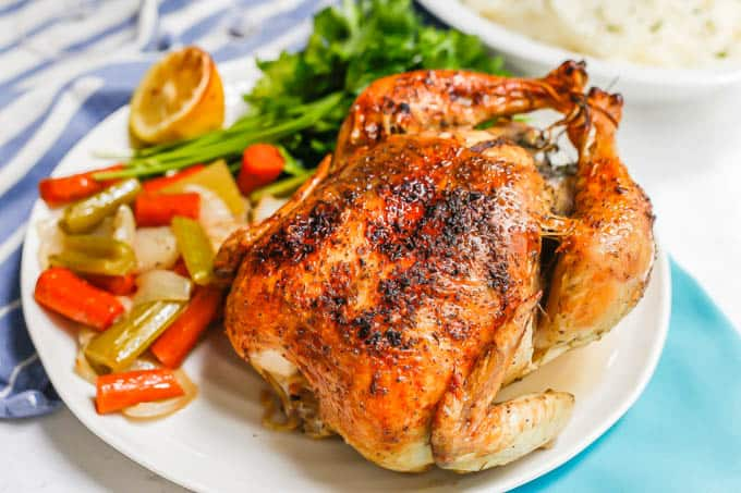 A whole roasted chicken served on a white platter with roasted veggies and lemon and parsley