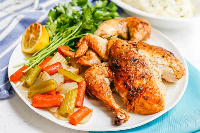A roasted and cut up chicken served with roasted veggies on a platter with lemon and parsley