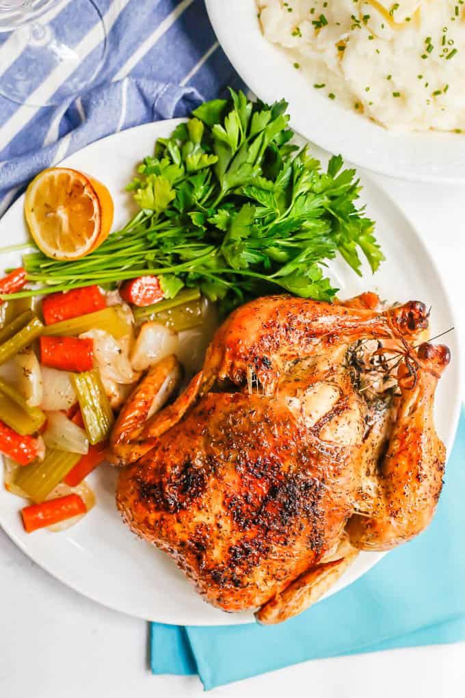 Overhead shot of an oven roasted chicken served with roasted veggies, parsley and lemon on a large white platter