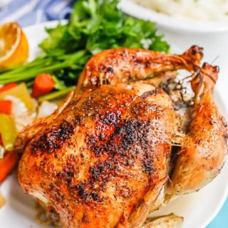 A browned and crispy whole roasted chicken on a platter with roasted veggies and fresh parsley