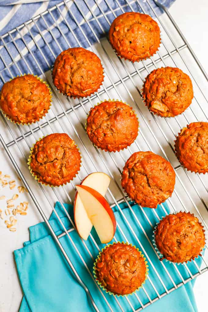 Overhead shot of a cooling rack with apple cider muffins and sliced apples and a sprinkling of oats