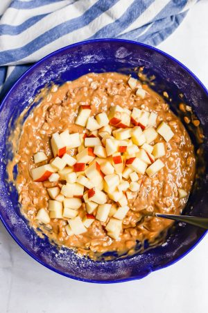 A blue bowl with muffin batter and chopped apples being added