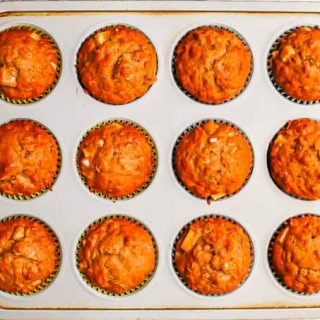 A dozen apple muffins in a muffin tin after baking