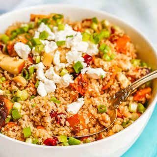 A large white bowl with a grain and veggie mix of quinoa, sweet potatoes, apples, feta cheese and green onions with a spoon resting in the bowl