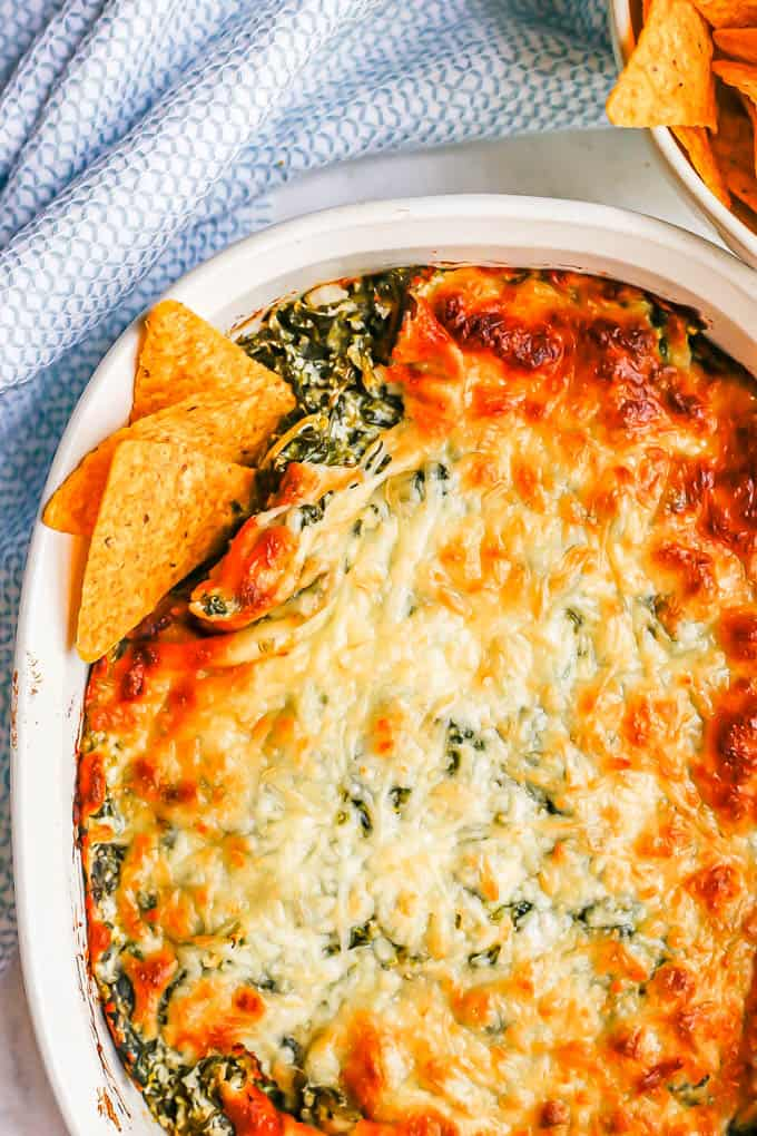 A browned and cheesy baked healthy spinach dip in a white casserole dish with tortilla chips tucked into the corner for dipping
