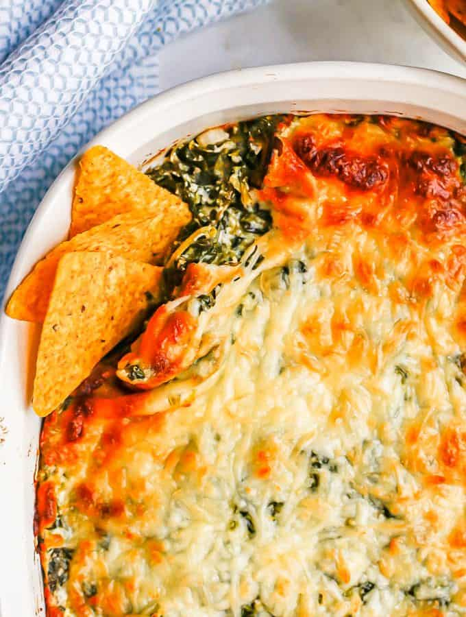 A browned and cheesy baked spinach dip in a white casserole dish with tortilla chips tucked into the corner for dipping