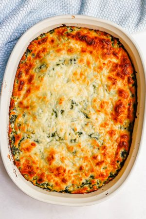 Browned, cheesy topped spinach dip in a white oval dish after baking