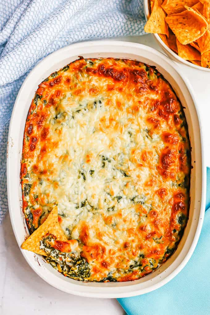 A baked spinach dip with a cheesy browned crust and a bowl of chips nearby for dipping