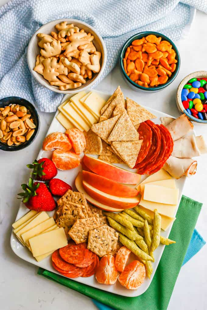 A large snack plate with cheese, crackers, cured meats, fruit and bowls of peanuts, animal crackers and Goldfish and M&Ms to the back