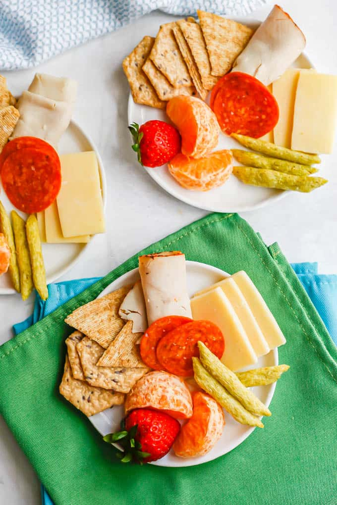 Individual snack plates for kids with cheese, crackers, turkey and fruit
