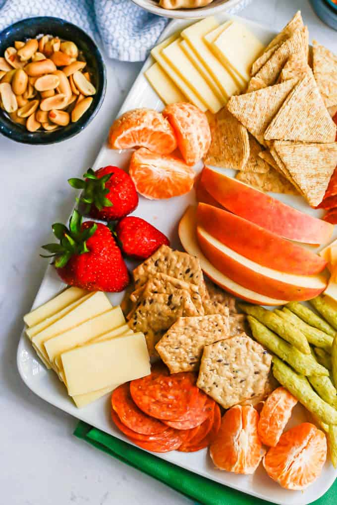 Close up of a charcuterie board for kids with cheese and crackers and fruit and a small bowl of peanuts to the side